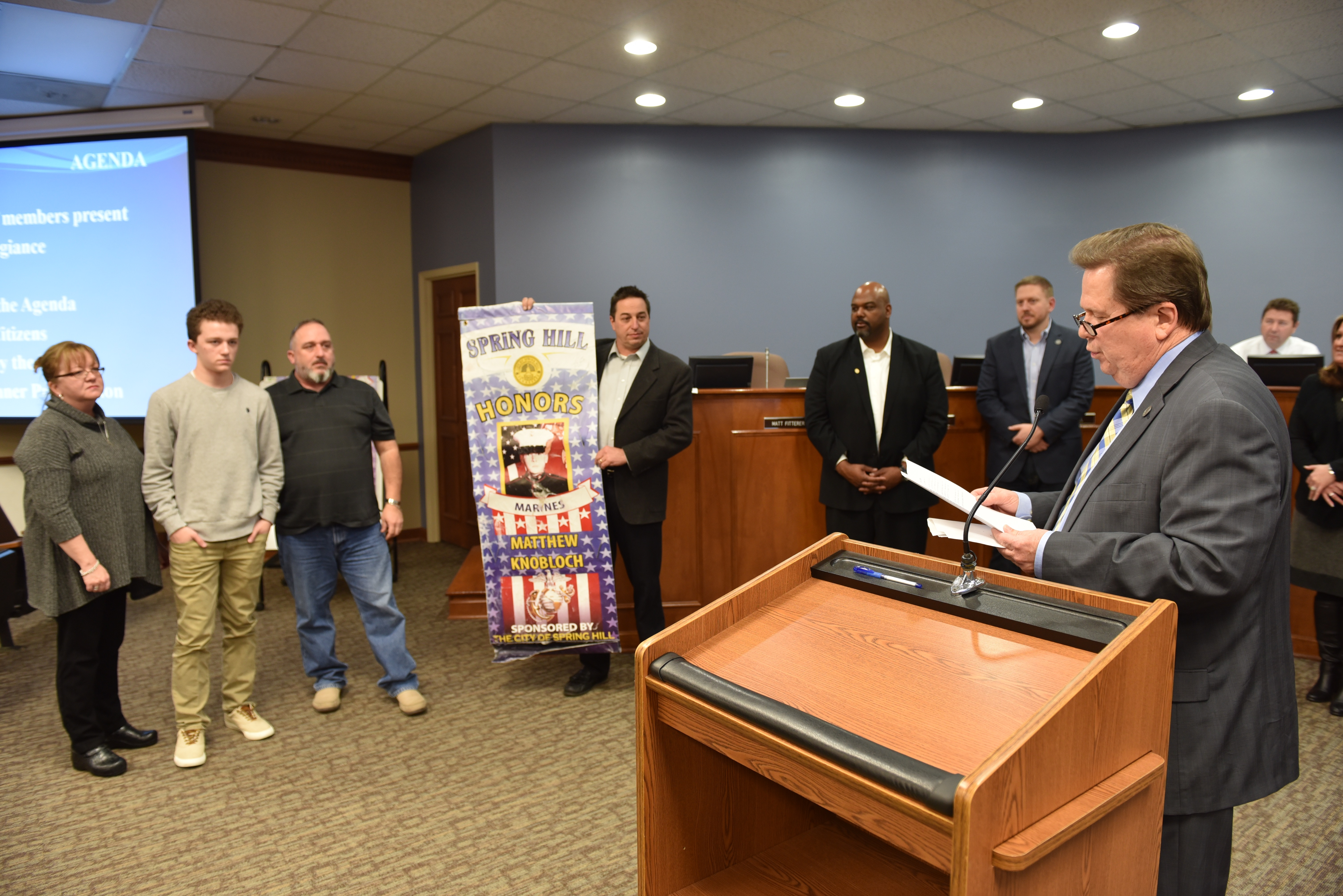 Mayor Graham presents a military service banner to Matthew Knobloch, U.S. Marine, at the Board of Mayor and Aldermen meeting